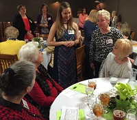 scholarship winner being introduced to women at a table