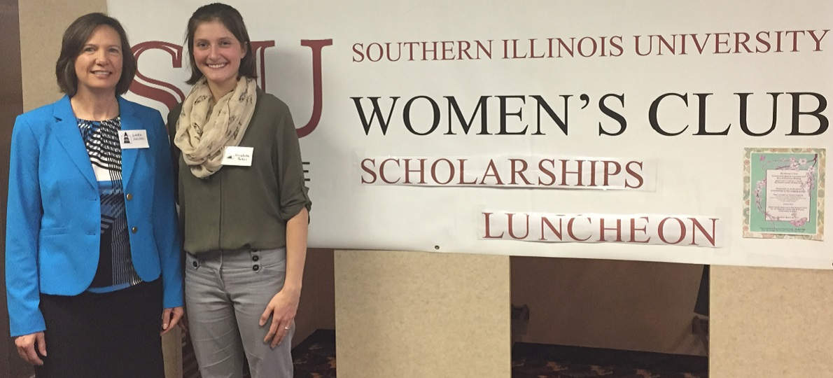 Scholarship director and winner standing in front of SIU Women's Club Banner